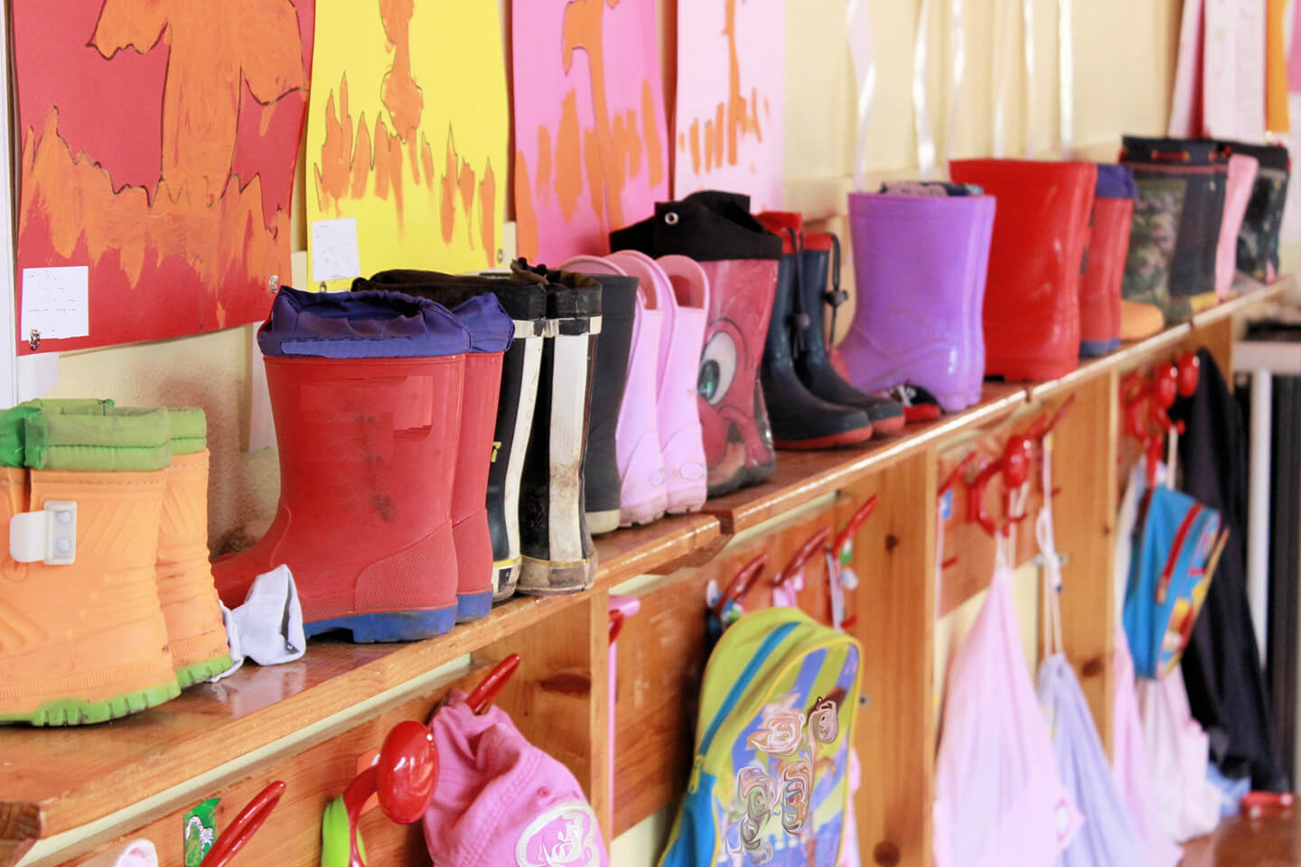 Childrens gum boots stacked on shelf at childcare center in the New England area near Coffs Harbour