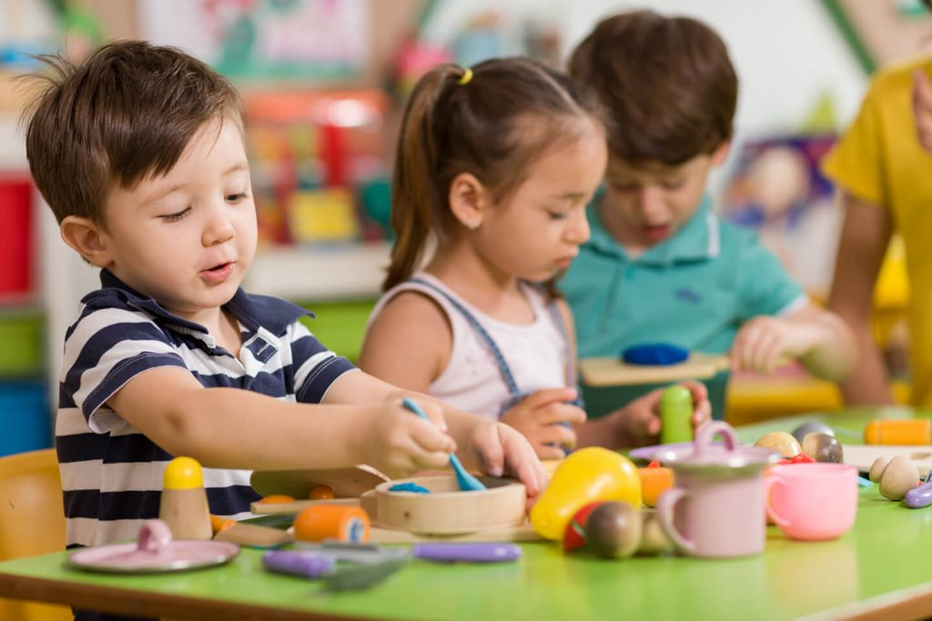 Young children playing with various toys on a table at a childcare center in the Newcastle area of NSW