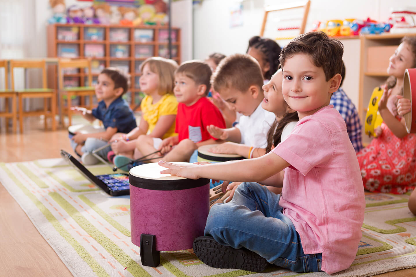 Young boy sitting on the floor patting a drum with other kids playing instruments at a childcare center in Parramatta, Blacktown Sydney