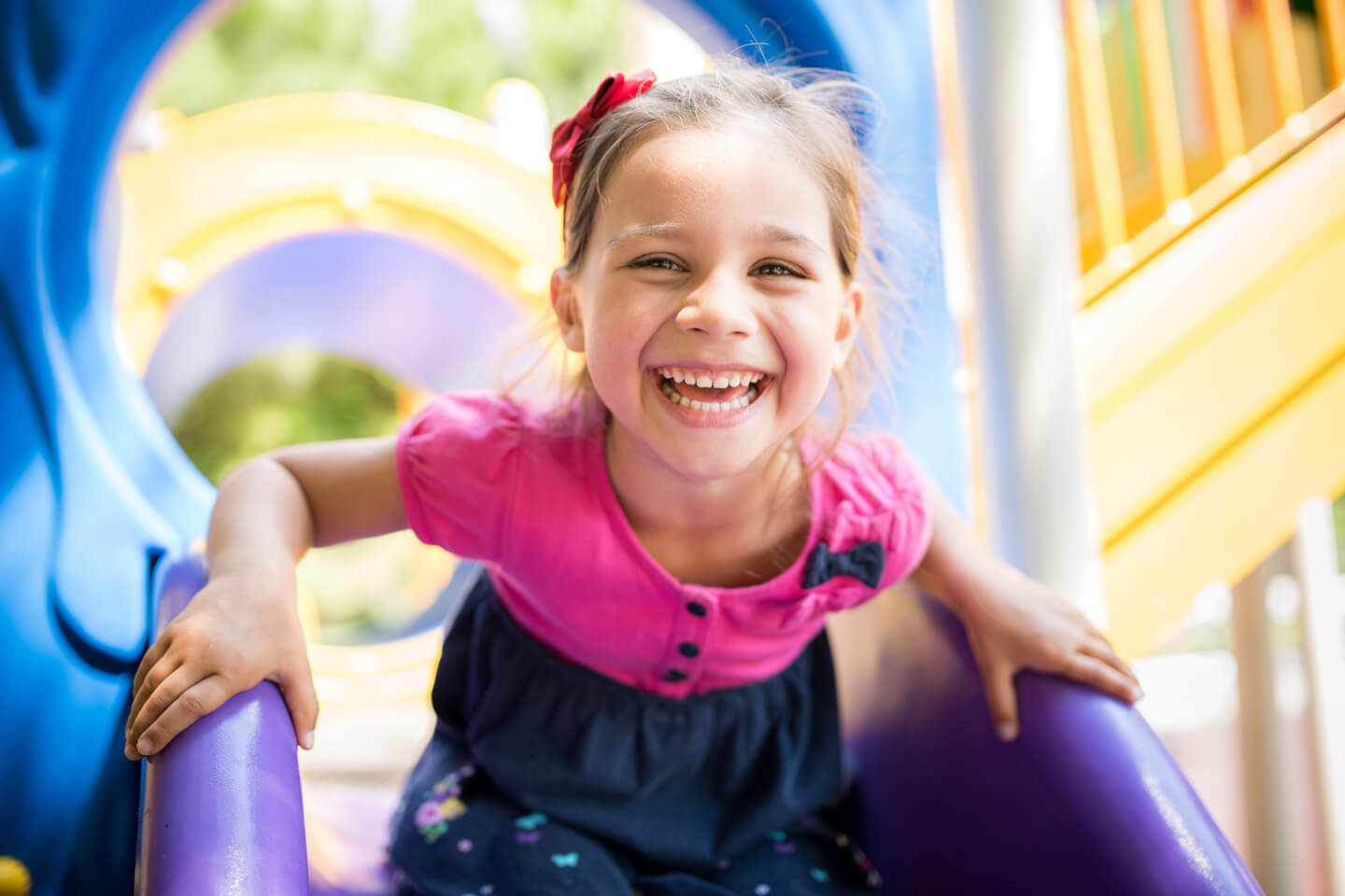 Young girl smiling while on a playground slide at a childcare center in the St George area of Sydney