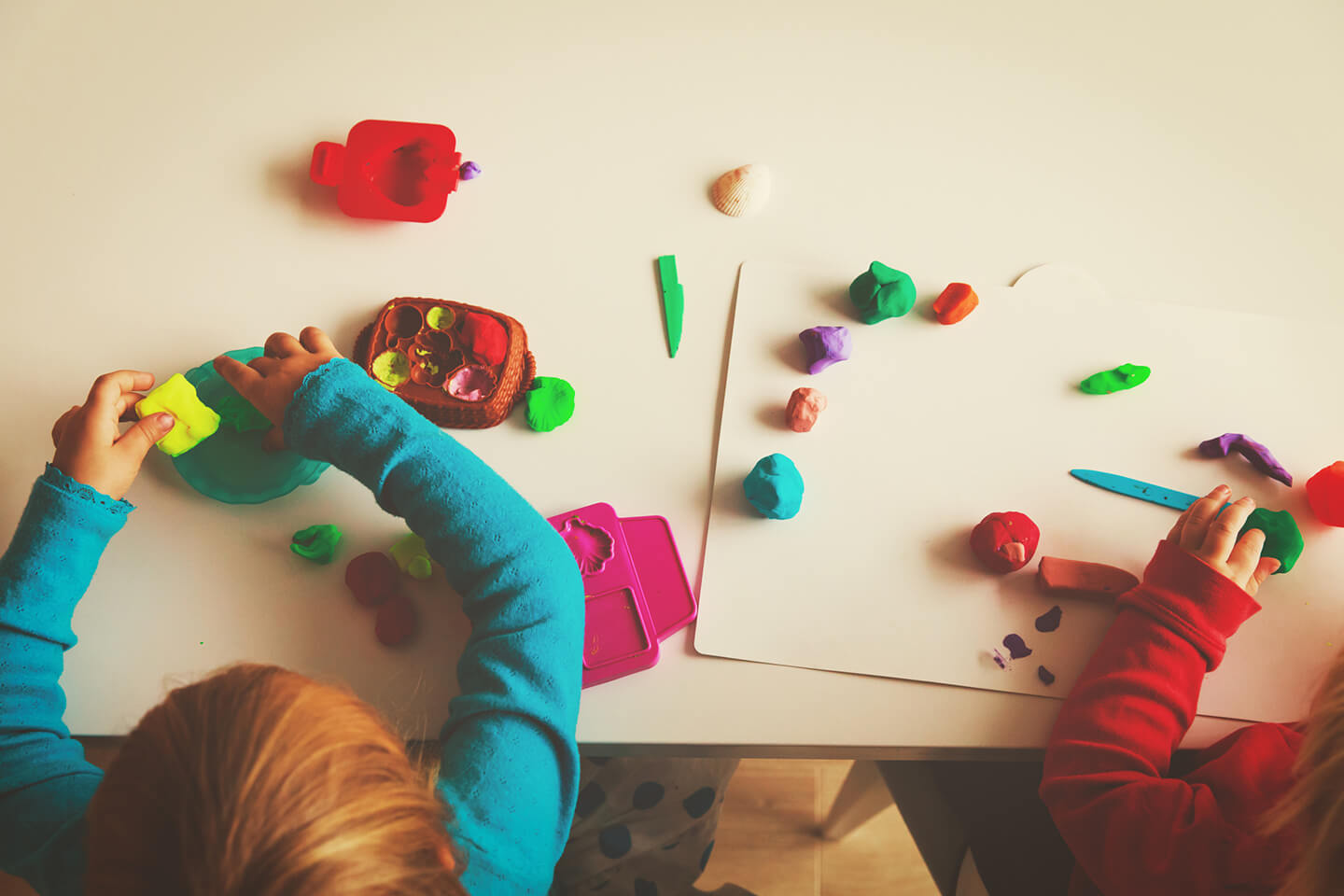 Young children playing with plasticine on a table at a childcare center in the Central Coast of NSW