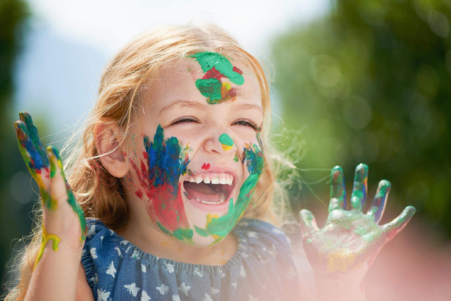 Young girl laughing while face painting on her face with her hands at a childcare center in Strathfield area Sydney
