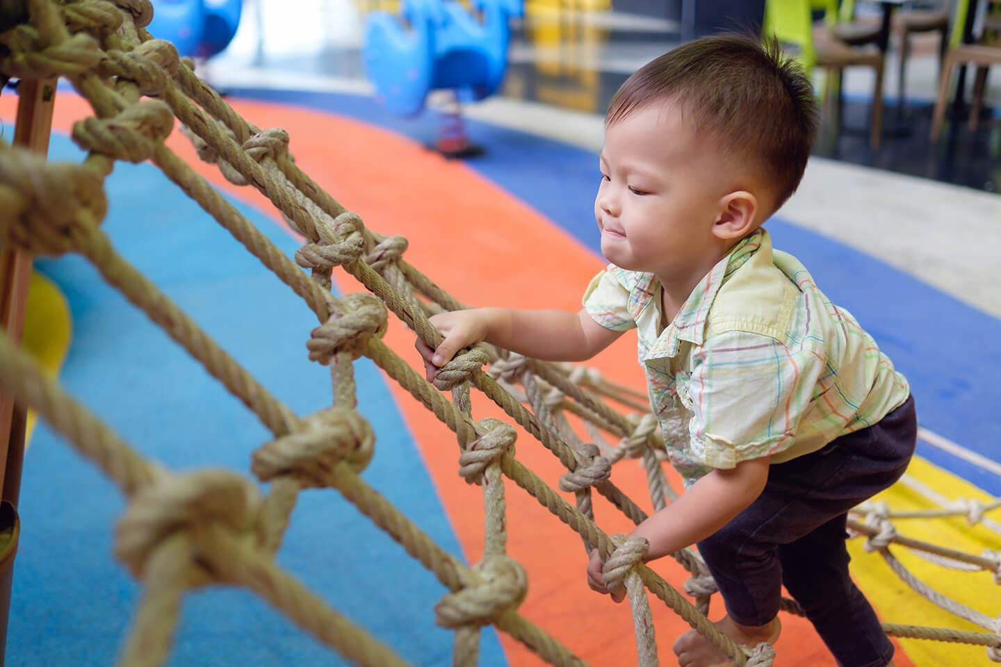 Young boy climbing up a cargo net at a childcare center in Campbelltown, Liverpool Sydney